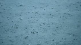 Chova as gotas que rippling em uma poça com reflexão do céu azul filme