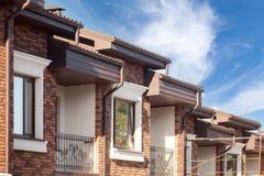 Chova a calha em uma casa moderna do tijolo com janelas plásticas imagens de stock royalty free