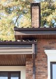 Chova a calha em uma casa moderna do tijolo com janelas plásticas fotos de stock royalty free