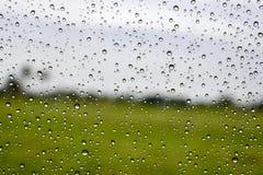 Chova a gota no fundo verde de vidro do carro Imagens de Stock