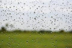 Chova a gota no vidro do carro, fundo abstrato do borrão Imagens de Stock