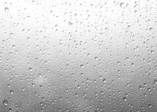 Chova gotas, gotas da água da chuva em um vidro de janela Luz borrada imagens de stock royalty free