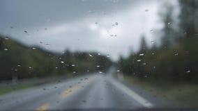 Chova gotas no para-brisa em conduzir o carro video estoque