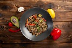 Chow νουντλς θαλασσινών στο μαύρο πιάτο στο ξύλινο υπόβαθρο στοκ φωτογραφίες