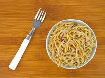 Chow Mein noodles with shrimp seasoning in bowl and fork Stock Photos
