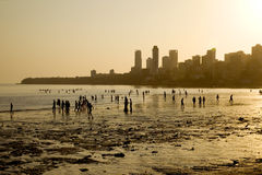 Chowpatty Beach at sunset, Mumbai, India. Locals walk on the beach in the early evening, with the skyscrapers of the city in the background, Chowpatty Beach at royalty free stock images