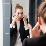 Choyer la belle jeune femme d'affaires vérifiant son mascara dans le miroir image libre de droits
