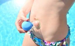 Choyer le concept La femme fait le massage mettant en forme de tasse de vide d'anti-cellulites sur un fond de l'eau bleue photo stock