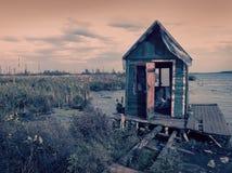 Choza abandonada terrible vieja asustadiza, casa espeluznante de madera en pantano deshabitado vacío misterioso con los árboles m fotos de archivo libres de regalías