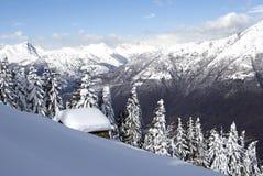 Choza alpestre bajo nieve imagenes de archivo