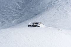 Choza alpina de la montaña aislada en campo de nieve windpacked imágenes de archivo libres de regalías