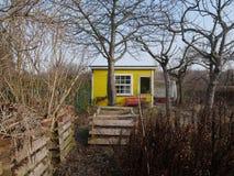 Choza amarilla brillante del jardín o pequeño hogar rústico Fotos de archivo