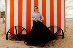 Choza de la arena del sol de la muchacha, De Panne, Bélgica foto de archivo