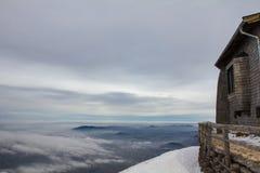 Choza en la montaña que pasa por alto el valle nevoso Fotografía de archivo