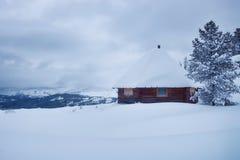 Choza en las montañas en la nieve foto de archivo
