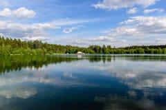 Choza roja en el bosque en la orilla del lago azul fotos de archivo libres de regalías