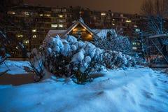 Choza y arbustos con el edificio alto de la nieve en la noche Imagenes de archivo