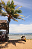 Choza y canoa tropicales de la playa Fotografía de archivo