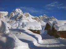 Chozas alpinas debajo de la nieve Fotografía de archivo libre de regalías