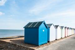 Chozas coloridas de la playa en una playa de Suffolk Imágenes de archivo libres de regalías