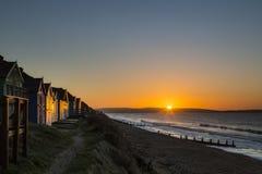 Chozas de la playa en la salida del sol Fotografía de archivo