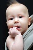 Chéri nouveau-née dans l'élingue grise Photographie stock