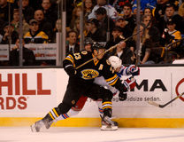 Chris Kelly checks Brandon Dubinsky (NHL). Boston Bruins forward Chris Kelly puts  New York Rangers forward Brandon Dubinsky against the boards Royalty Free Stock Photography