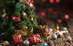 Chrismas-Baum mit Geschenk auf altes Holz und rotes Licht bokeh, Lizenzfreie Stockfotografie