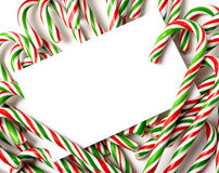 Chrismas Candy Cane Notecard or Invitation. A white notecard, greeting card, or invitation surrounded by brightly color Christmas Candy Canes with copy space Royalty Free Stock Image