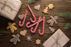 Chrismas cookies, candy canes on wooden background. Holiday mood. Top view. Stock Images