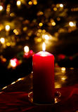 Chrismas eve at home, red candle lit and blurred lights Royalty Free Stock Photography