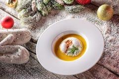 Chrismas-Fischsuppe in der weißen Platte mit Weihnachtsdekorationen, moderne Gastronomie Lizenzfreies Stockbild