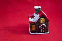 Chrismas or new year candle house. On red cloth Stock Images