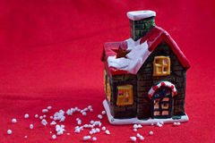 Chrismas or new year house candle. On red cloth Royalty Free Stock Images
