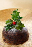 Chrismas pudding with holly twig on golden Royalty Free Stock Image