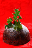 Chrismas pudding with holly twig on red paper Stock Photo