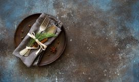Christmas table place setting. Tableware with evergreen twigs, co. Christmas table place setting. Tableware, evergreen twigs, cone and spice. New Year food royalty free stock photo