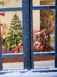 Chrismas window. Little girl opening a Christmas present watched from a snowy window Stock Image
