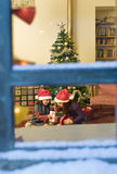 Chrismas window. Two little girls opening Christmas presents watched from a snowy window Royalty Free Stock Photography