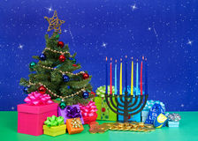 Chrismukkah. Christmas tree with presents next to Hanukkah menorah burning candles, dreidel, chocolate gold coin gifts. Many multi faith families celebrate both Royalty Free Stock Photo