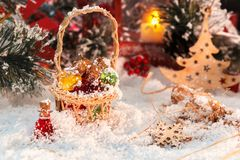 Chrissmall multi-colored glass bottlestmas present and Christmas ball on snow against a background of shiny tinsel. glowing lights Stock Photo