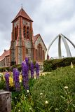 Christ Church Cathedral and Whale Bone Arch, with flowers and garden in the foreground. Port Stanley, Falkland Islands royalty free stock photo