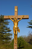 Christ on the cross. A golden figure of Christ hangs on a cross in rural France stock images
