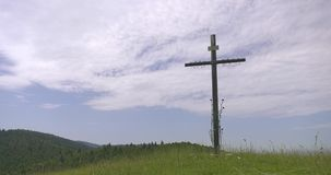 Christ cross on hill. Jesus cross on hill with mountain meadow and moving clouds in blue sky stock footage