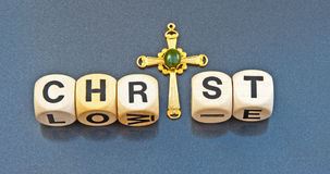 Christ and the cross. ' Christ ' in upper case black text on small white cubes with letter ' i' replaced with a gold cross isolated on a gray background Stock Image