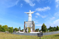 Christ the Redeemer Statue in Papua Island. Portrait of the Jesus Christ with open hand and a sign for a the tree (Pometia pinnata) which was planted by The Royalty Free Stock Images