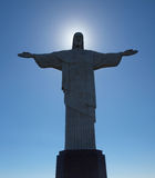 Christ the redeemer with sun behind his head. Christ the redeemer with the sun shining behind his head stock photography