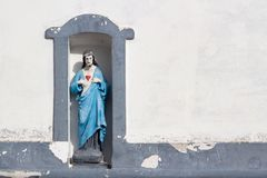 Christ sculpture on facade of rural house royalty free stock image