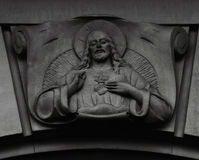 Christ. Shot in black and white, detail on an sculpture representing an image of Jesus Christ placed on the facade of this historic building, set in Eixample Royalty Free Stock Photos