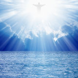 Christ in skies. Christ silhouette in blues skies over sea, bright light from heaven stock photo